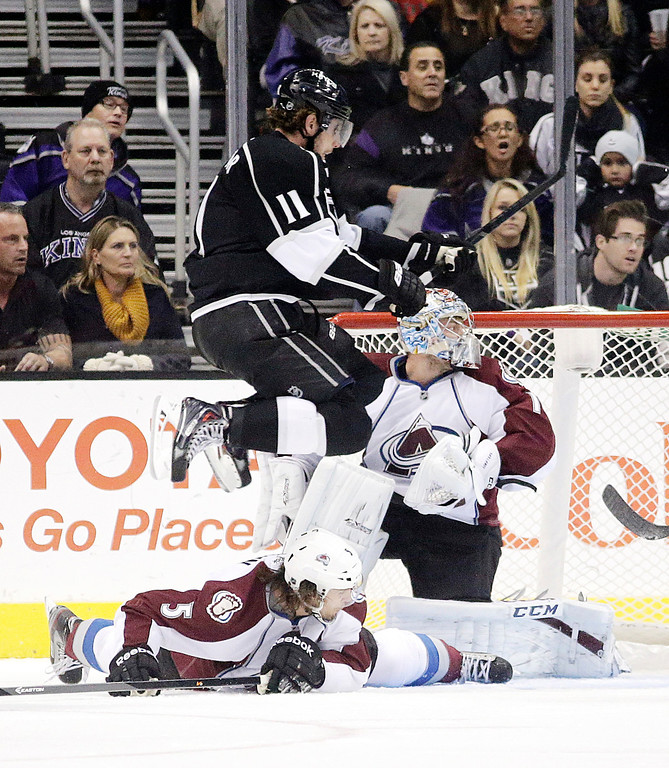 . Los Angeles Kings\' Anze Kopitar, top, of Slovenia, jumps in front of Colorado Avalanche goalie Semyon Varlamov, right, of Russia, to avoid Colorado Avalanche\'s Nate Guenin during the first period of an NHL hockey game on Saturday, Nov. 23, 2013, in Los Angeles. (AP Photo/Jae C. Hong)
