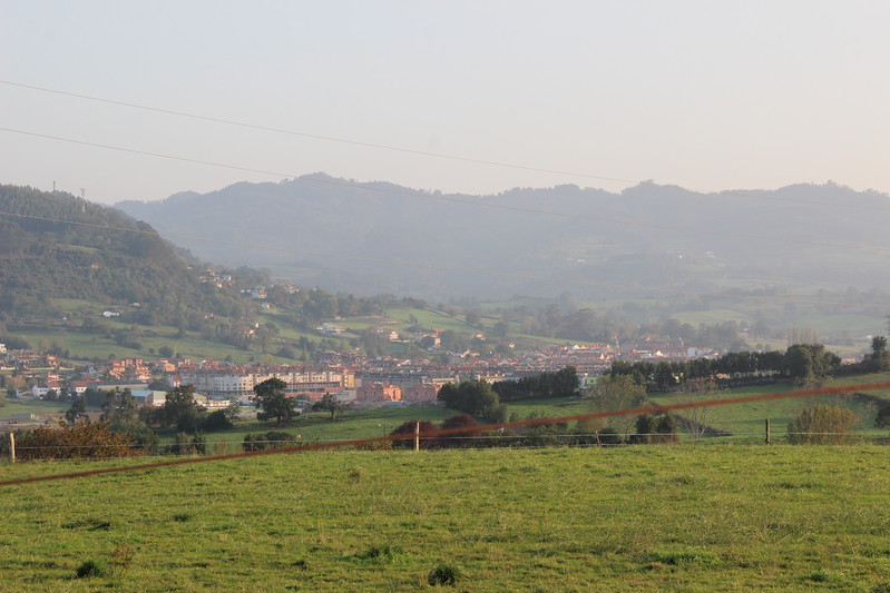 Mountains and green grass frame the view of the Asturias landscape in Spain.