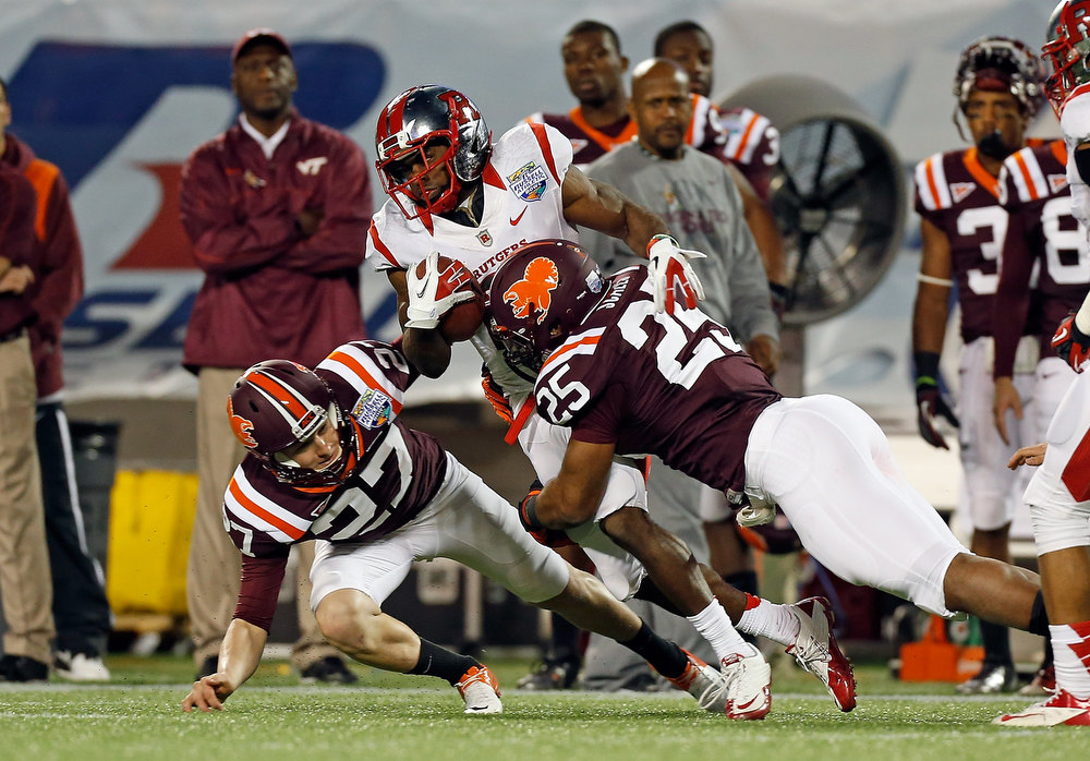 . Punt return man Mason Robinson #24 of the Rutgers Scarlet Knights is tackled by Martin Scales #25 and A.J. Hughes #27 of the Virginia Tech Hokies during the Russell Athletic Bowl Game at the Florida Citrus Bowl on December 28, 2012 in Orlando, Florida.  (Photo by J. Meric/Getty Images)