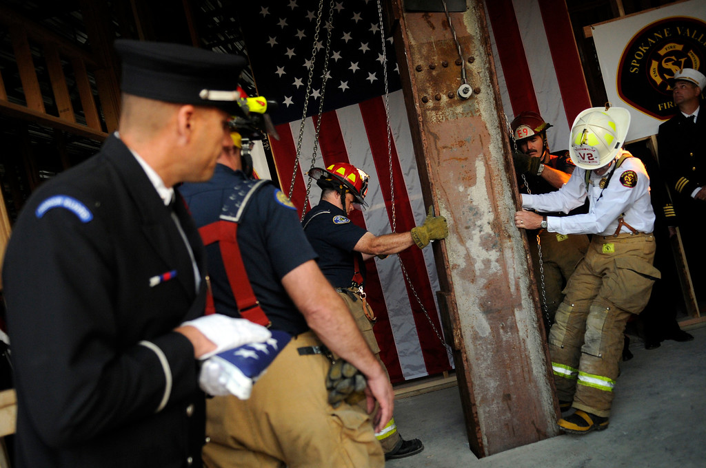 . In this Sunday, Sept. 11, 2011 file photo, Spokane Valley Fire Department Deputy Chief Larry Rider, far right in white, and SVFD Captain Tag Baugh adjust a 1,200 pound beam recovered from the World Trade Center into it\'s final resting spot in a ceremony at the new SVFD administration building on the tenth anniversary of the Sept. 11, 2001 terrorist attacks, in Spokane Valley, Wash. Artifacts have gone to 1,585 fire and police departments, schools and museums, and other nonprofit organizations in every state and at least eight other countries. (J. Bart Rayniak/The Spokesman-Review via AP)