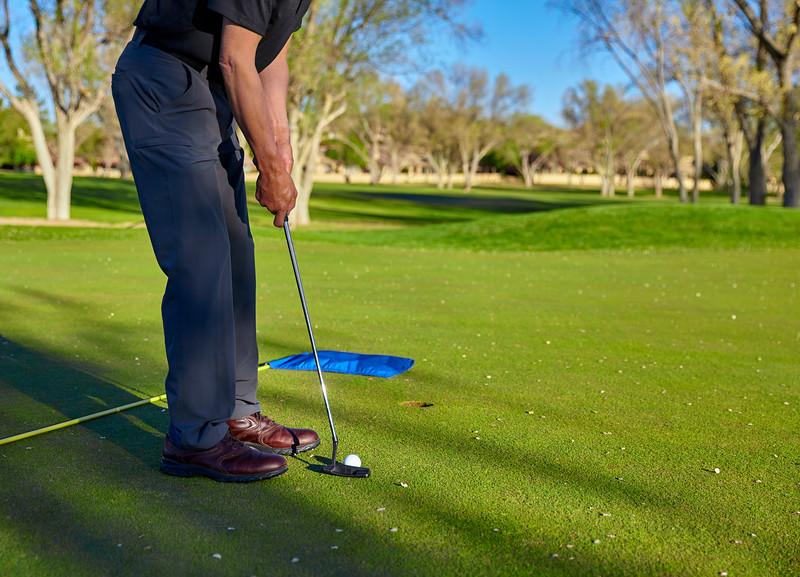 Man golfer putting green late afternoon golf round