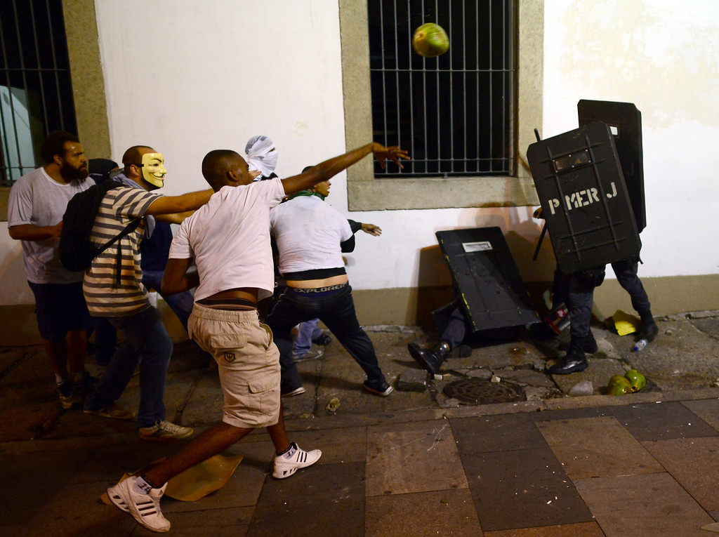 . A demonstrator throws a coconut at anti riot policemen during clashes in downtown Rio de Janeiro on June 17, 2013, after a protest against higher public transportation fares and the use of public funds to finance international football tournaments. Protesters in several major cities are up in arms over hikes in mass transit prices -- from $1.5 to $1.6 -- as well as over the $15 billion earmarked for the two sports events amid calls for more health and education funding. CHRISTOPHE SIMON/AFP/Getty Images