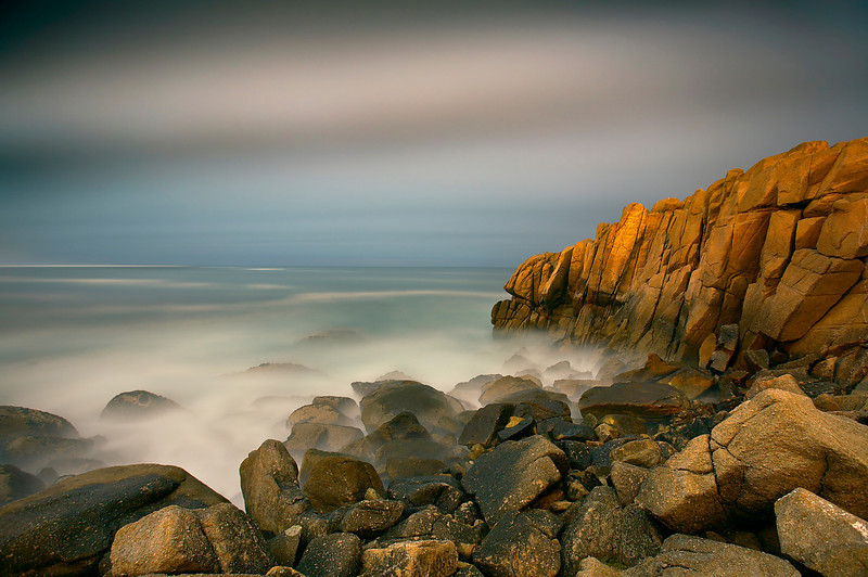 The clouds opened up and let the moonlight through to the rocks and sea on a foggy Monterey night. The violent surf was smoothed out by a long exposure, making this place look like another world.   Fog at night creates a lot of atmosphere even though the stars are not visible.    Because the fog came and went and I was making long exposures, some images were underexposed while others were overexposed.  It really is a matter of luck in situations like this, so I spent a few hours making just a few images, of which only this one turned out well.  Time well spent I believe!.