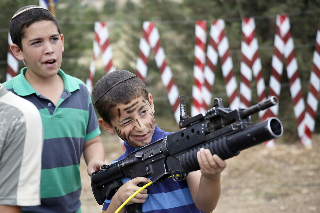 . An Israeli boy plays with an M-16 rifle during a traditional military weapon display to mark the 66th anniversary of Israel\'s Independence at the West Bank settlement of Efrat on May 6, 2014 near the biblical city of Bethlehem. Israelis are marking Independence Day, celebrating the 66th year since the founding of the Jewish State in 1948 according to the Jewish calendar. AFP PHOTO/GALI TIBBON