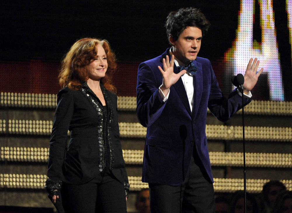 . Recording artists Bonnie Raitt, left, and John Mayer present at the 55th annual Grammy Awards on Sunday, Feb. 10, 2013, in Los Angeles. (Photo by John Shearer/Invision/AP)