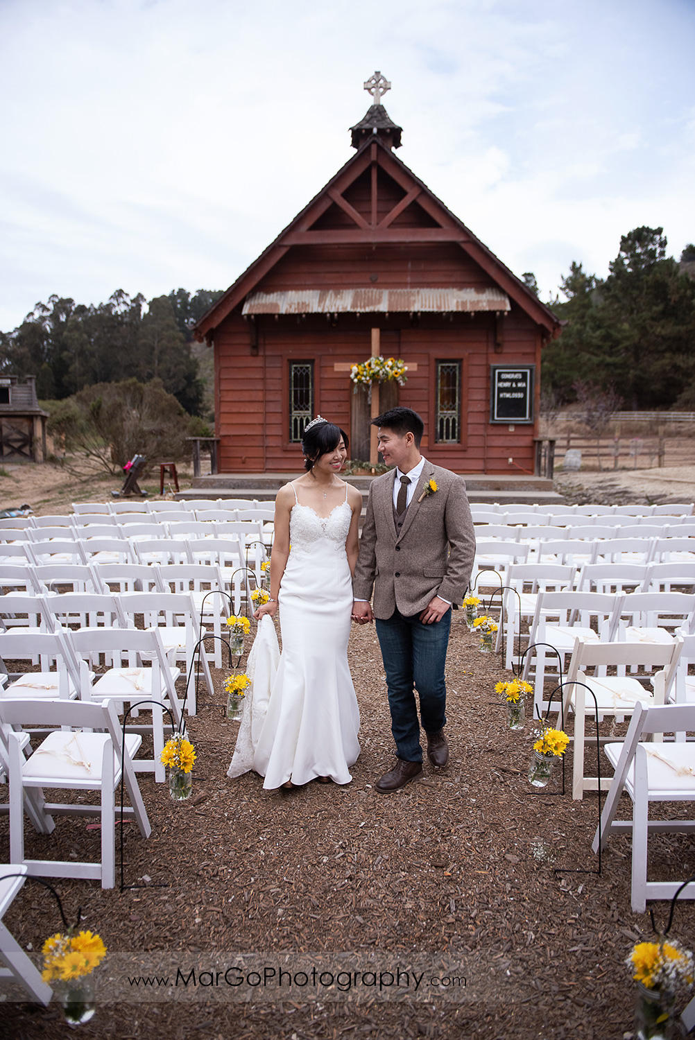 bride and groom holding hands and walking in forn of small church at Long Branch Saloon & Farms in Half Moon Bay