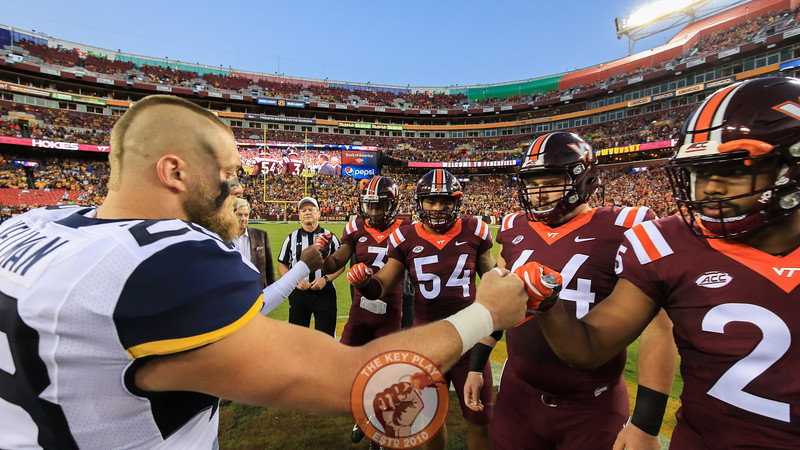 The two sets of captains greet each other at midfield for the coin toss. (Mark Umansky/TheKeyPlay.com)