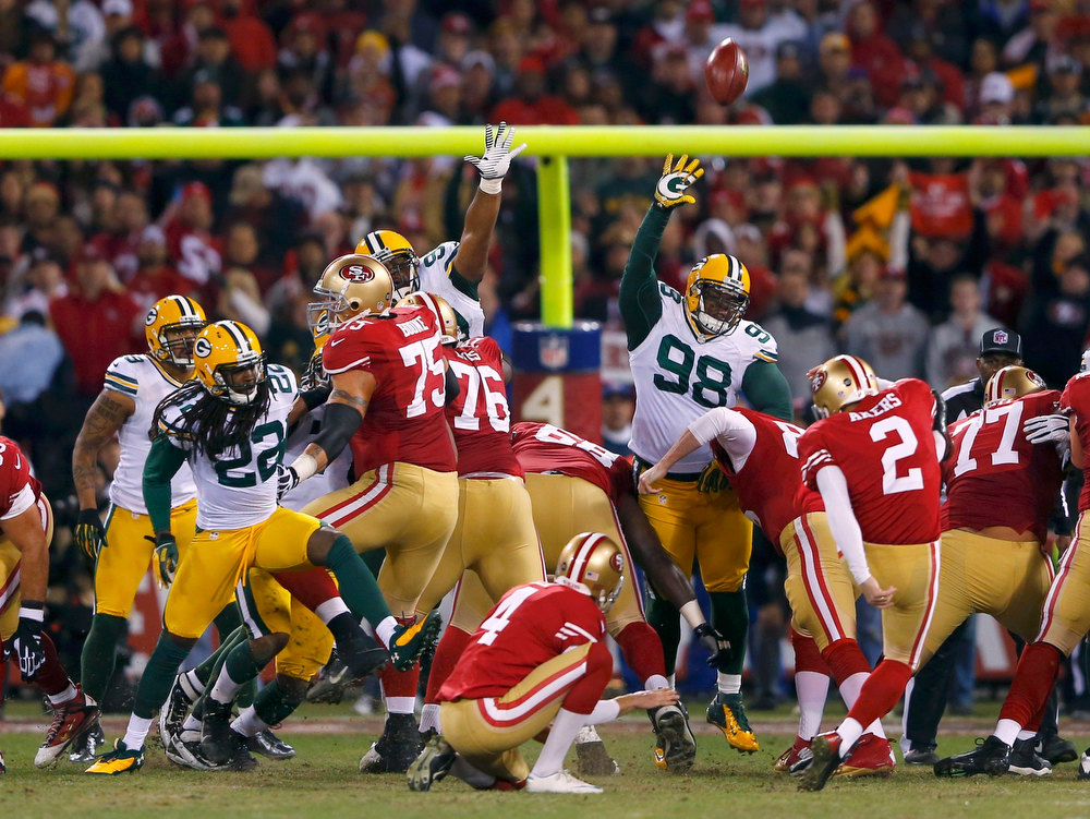 Description of . San Francisco 49ers kicker David Akers (R) kicks a field goal past Green Bay Packers C.J. Wilson in the second quarter during their NFL NFC Divisional playoff football game in San Francisco, California, January 12, 2013. REUTERS/Mike Blake