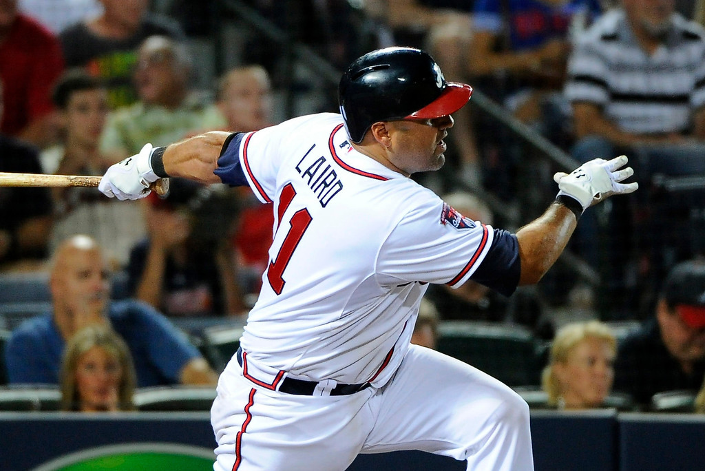 . Atlanta Braves\' Gerald Laird follows through on an RBI single against the Colorado Rockies to break a 2-2 tie during the eighth inning of a baseball game Friday, May 23, 2014, in Atlanta. (AP Photo/David Tulis)