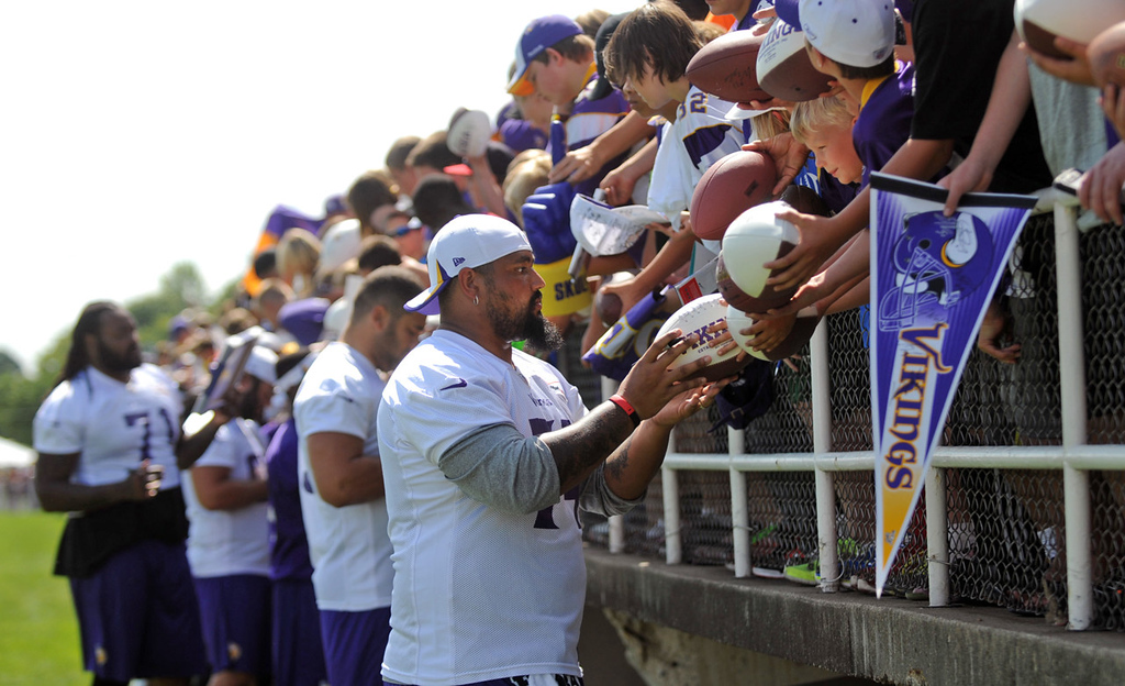 . Offensive guard Charlie Johnson, center, and his fellow offensive line teammates work the stands in Blakeslee Stadium on the last day of training camp. (Pioneer Press: Chris Polydoroff)