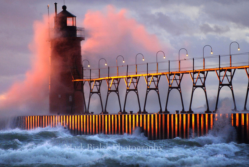 High winds spray water over the South Haven lighthouse as the warm setting sun reflects off the pier Sunday evening.  Some, standing on the beach, braved the high winds and experienced a dramatic, turbulent and colorful mid-November sunset as others watched from the comfort of their cars.