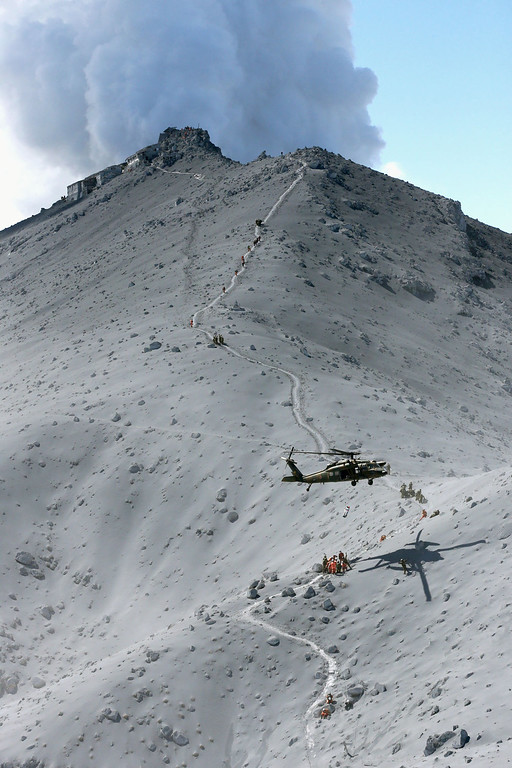 . Firefighters and members of Japan\'s Self-Defense Forces conduct a rescue operation near the peak of Mount Ontake as plumes of smoke billow in central Japan, Sunday, Sept. 28, 2014. Mount Ontake erupted shortly before noon Saturday, spewing large white plumes of gas and ash high into the sky and blanketing the surrounding area in ash. Rescue workers on Sunday found more than 30 people unconscious and believed to be dead near the peak of an erupting volcano, a Japanese police official said. (AP Photo/Kyodo News)