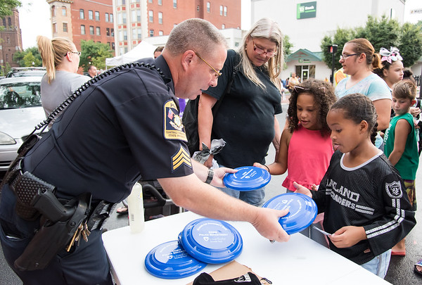 08/07/18 Wesley Bunnell | Staff New Britain Police held their annual National Night Out 2018 on Tuesday evening in a blocked off Central Park area. CCSU Police Sgt. Jerry Erwin hands out frisbees to Marley Mitchell, age 8 middle, and Briseyis Luke, age 9.
