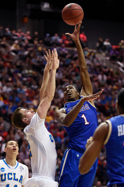 . Tulsa forward Rashad Smith, right, shoots over UCLA forward David Wear during the first half of a second-round game in the NCAA men\'s college basketball tournament Friday, March 21, 2014, in San Diego. (AP Photo/Denis Poroy)