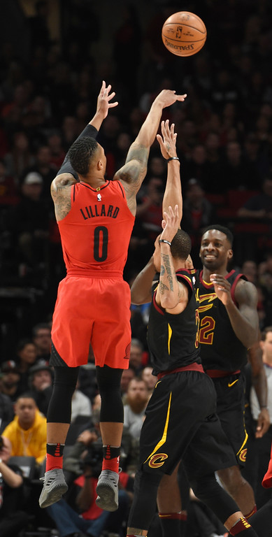. Portland Trail Blazers guard Damian Lillard, left, hits a shot over Cleveland Cavaliers guard George Hill, right, during the first half of an NBA basketball game in Portland, Ore., Thursday, March 15, 2018. (AP Photo/Steve Dykes)