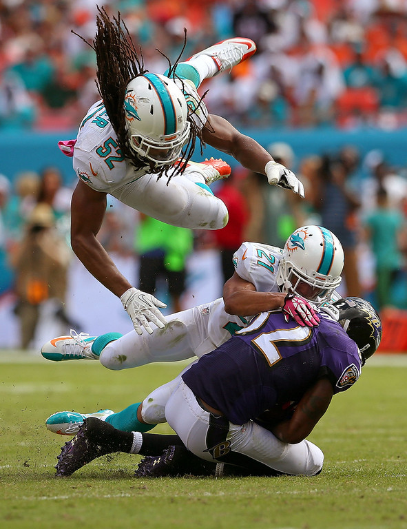 . Philip Wheeler #52 of the Miami Dolphins flies over Brent Grimes #21 as he tackles Torrey Smith #82 of the Baltimore Ravens  during a game  at Sun Life Stadium on October 6, 2013 in Miami Gardens, Florida.  (Photo by Mike Ehrmann/Getty Images)