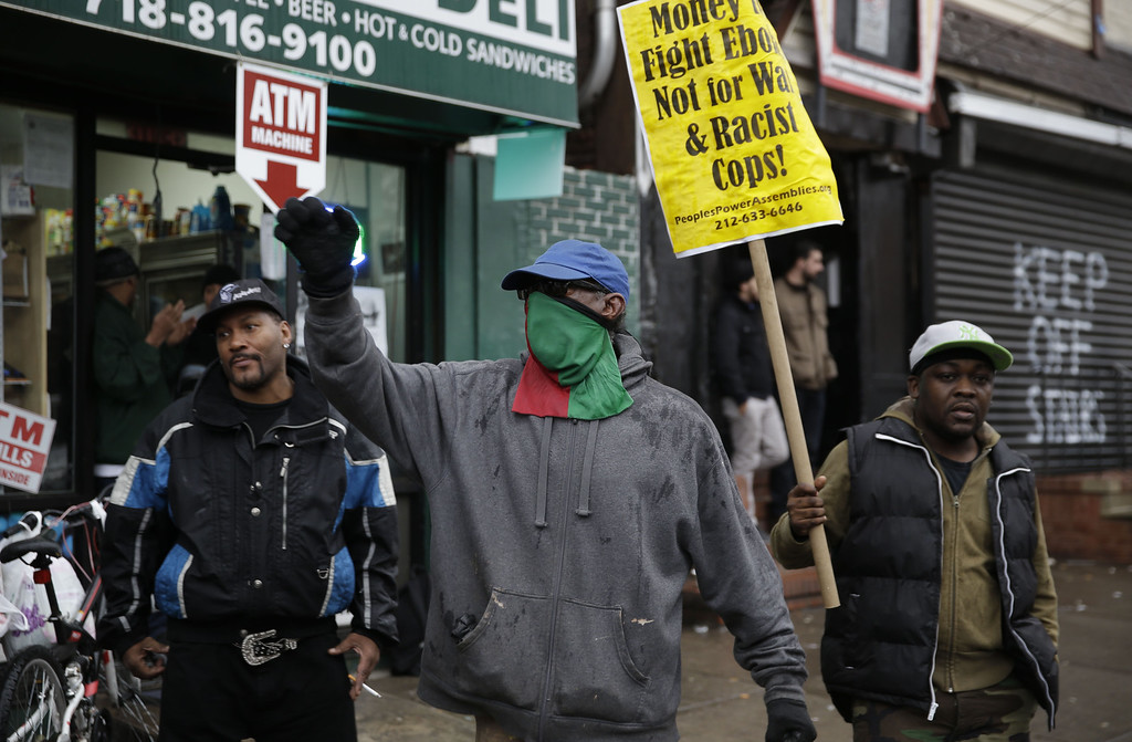 . A man yells and chant slogans near the site of Eric Garner\'s death after it was announced that the officer that killed him is not being indicted in the borough of Staten Island in New York, Wednesday, Dec. 3, 2014. A grand jury cleared the white New York City police officer Wednesday in the videotaped chokehold death of Garner, an unarmed black man, who had been stopped on suspicion of selling loose, untaxed cigarettes, a lawyer for the victim\'s family said.  A video shot by an onlooker and widely viewed on the Internet showed the 43-year-old Garner telling a group of police officers to leave him alone as they tried to arrest him. The city medical examiner ruled Garner\'s death a homicide and found that a chokehold contributed to it. (AP Photo/Seth Wenig)