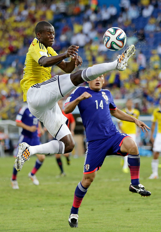 . Colombia\'s Adrian Ramos tries to control the ball against Japan\'s Toshihiro Aoyama during the group C World Cup soccer match between Japan and Colombia at the Arena Pantanal in Cuiaba, Brazil, Tuesday, June 24, 2014.(AP Photo/Dolores Ochoa)
