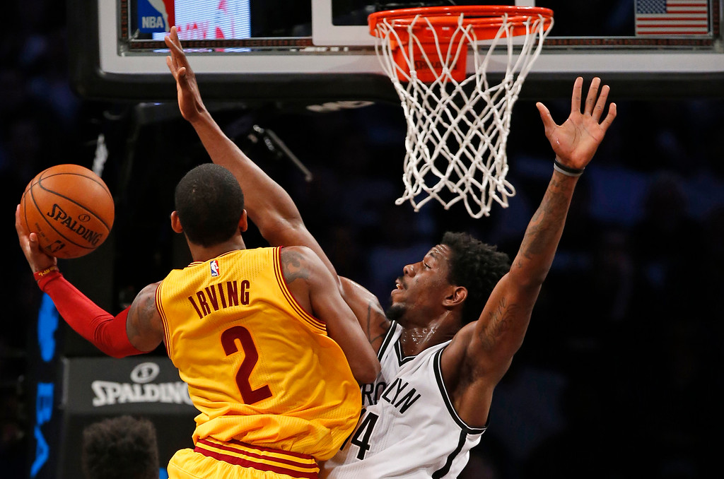 . Brooklyn Nets center Henry Sims (14) blocks Cleveland Cavaliers guard Kyrie Irving (2) in the second half of an NBA basketball game, Thursday, March 24, 2016, in New York. The Nets beat the Cavaliers 104-95. (AP Photo/Kathy Willens)
