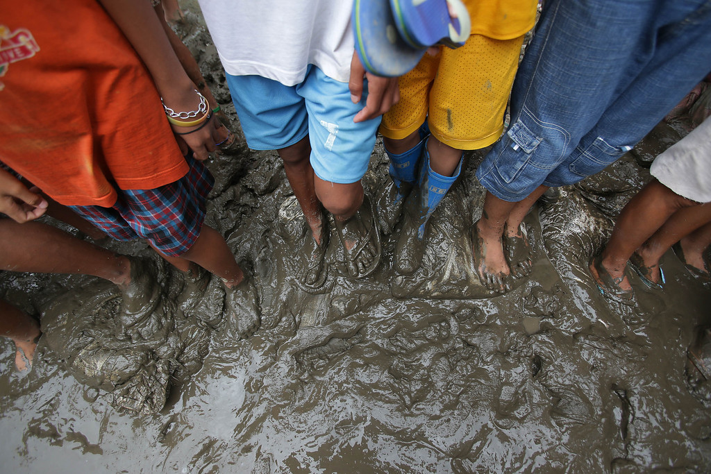 . Filipino residents step on muddied streets outside their homes as they wait for local celebrities donating goods to flood affected communities living near the banks of the swollen Laguna lake in Laguna province, southern Philippines on Thursday, Aug. 22, 2013. Lashed each year by typhoons and stuck with outdated drainage systems, the Philippine capital has been hit by ever-worsening floods. Manila is located in a catch basin sandwiched between Manila Bay and Lake Laguna to the southeast. (AP Photo/Aaron Favila)