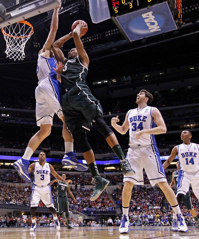 . Michigan State forward Adreian Payne (5) goes up with a shot against Duke forward Mason Plumlee during the first half of a regional semifinal in the NCAA college basketball tournament, Friday, March 29, 2013, in Indianapolis. Watching is Duke\'s Ryan Kelly (34). (AP Photo/Michael Conroy)