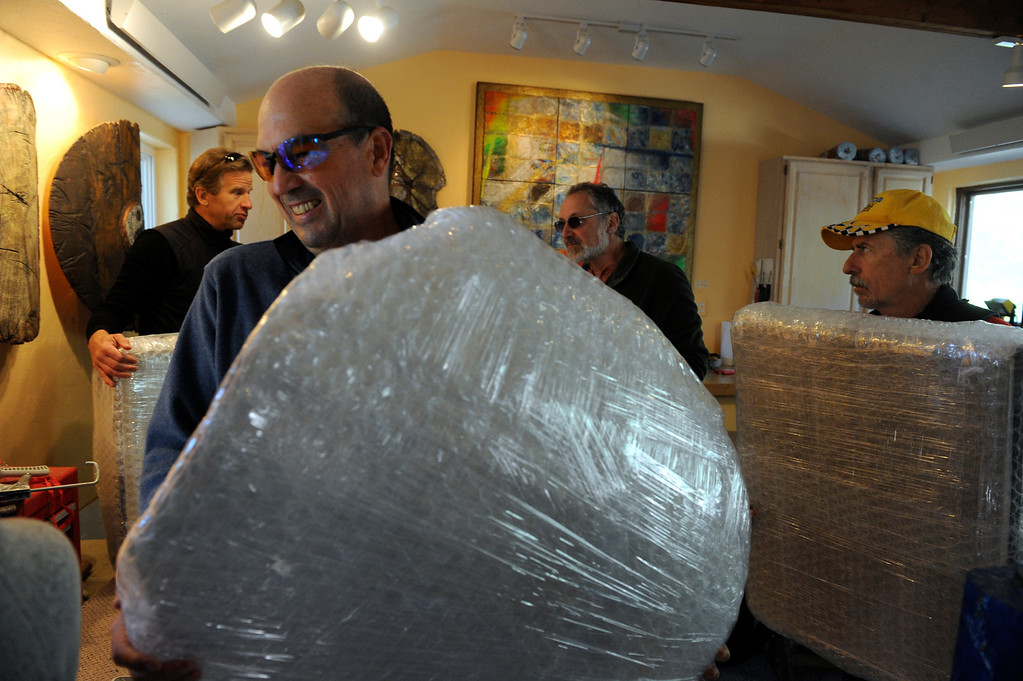 . BOULDER, CO - Sept. 28: Inside his studio, Jeff Dahoda, left, Peter Oatman, second from left, and Jeff Fitzgerald, right,  start to carry some of Montanari\'s, (background) work out to the driveway. Friends and fellow Boulder artists gather to hike in to the home and studio of artist Marco Montanari to rescue and carry out his Encaustic paintings that need to be packed and sent to New York for a show in November. Montanari\'s home and studio did not suffer damage in the floods, but all roads leading in and out had been impassable up until just a few days ago. The group was able to drive a short distance up Wagon Wheel Gap Road and hiked the rest of the way in and out. (Photo By Kathryn Scott Osler/The Denver Post)