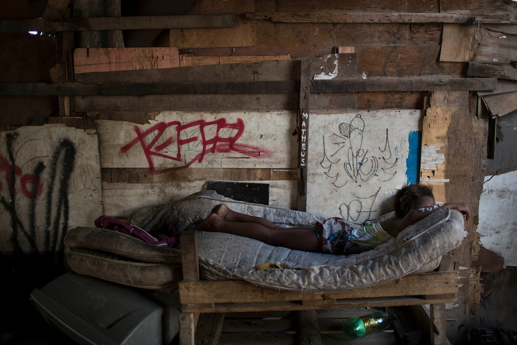 . A girl lays on a mattress placed under a bridge in a poor area of the Mare slum complex in Rio de Janeiro, Brazil, Saturday, April 5, 2014. More than 2,000 Brazilian soldiers stormed into the slum complex Saturday with armored personnel carriers and helicopters in a bid to improve security two months before the start of the World Cup. (AP Photo/Felipe Dana)