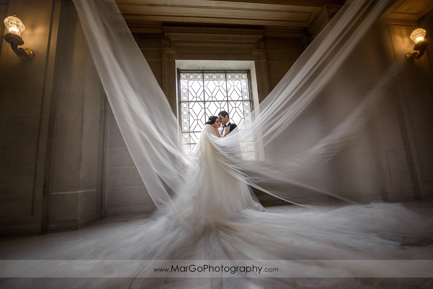 veil shot of bride and groom in San Francisco City Hall