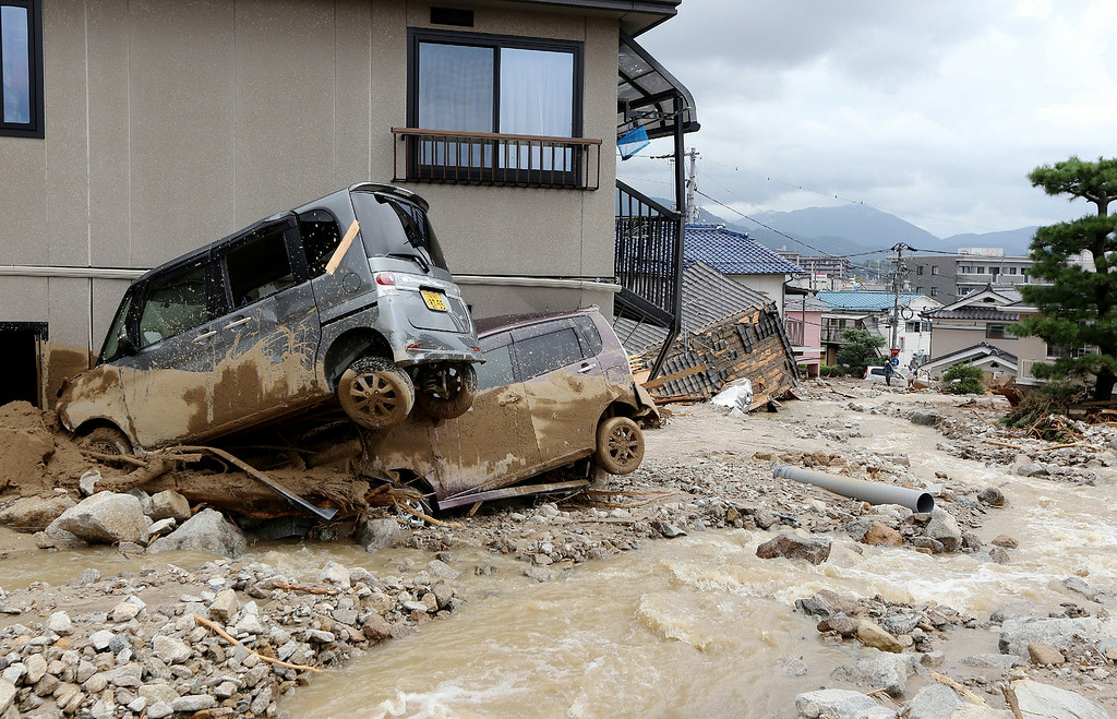 . Cars damaged by a landslide lie in mud and debris after heavy rains hit the city of Hiroshima, western Japan, on August 20, 2014.    AFP PHOTO/Jiji PressJIJI PRESS/AFP/Getty Images