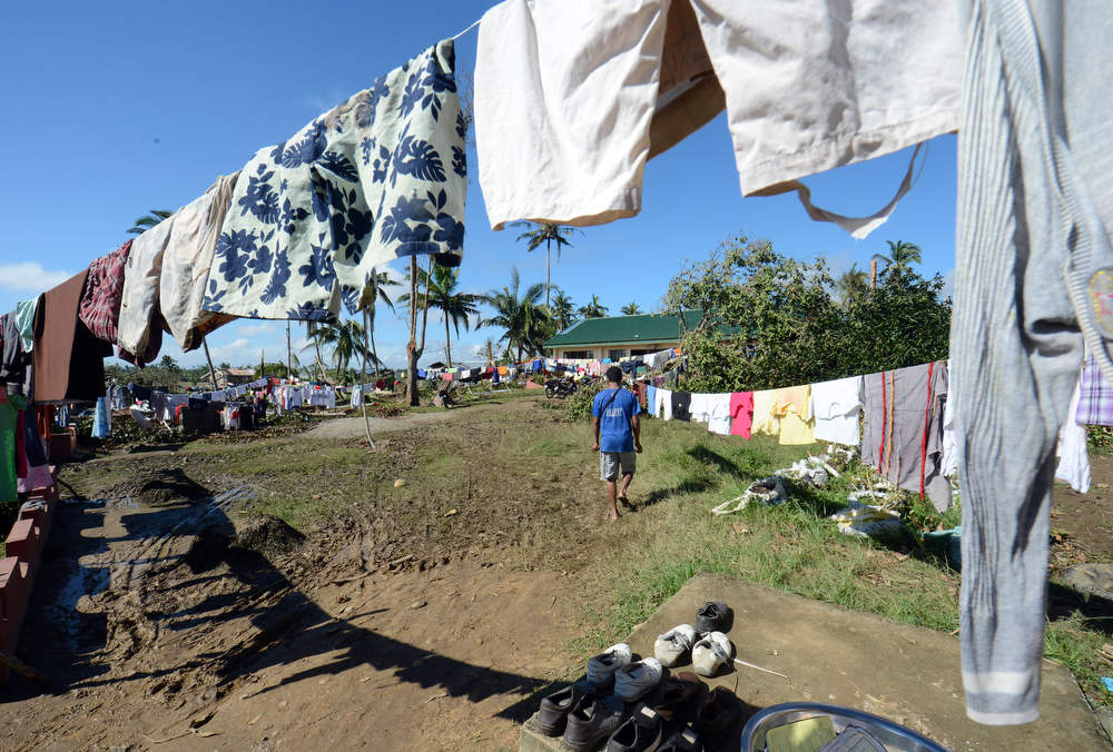Description of . A resident (C) walks past a clothes line at a school serving as an evacuation center for victims of Typhoon Bopha in the town of Maparat in Compostela Valley province on December 8, 2012.  Hungry and homeless typhoon survivors appealed for help on December 8 as the ravaged southern Philippines mourned its more than 500 dead and desperate people in one hard-hit town looted shops in search of food.     AFP PHOTO / TED  ALJIBE/AFP/Getty Images