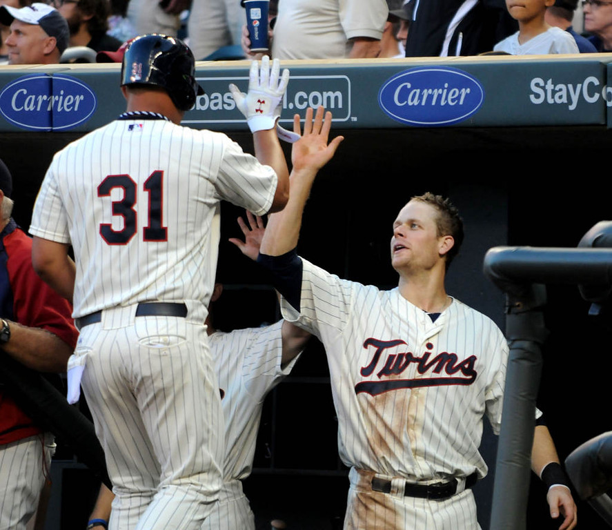 . Minnesota\'s Justin Moreau celebrates a run with teammate Oswaldo Arcia after Arcia scored on Trevor Plouffe\'s single during the seventh inning.(Pioneer Press: Sherri LaRose-Chiglo)