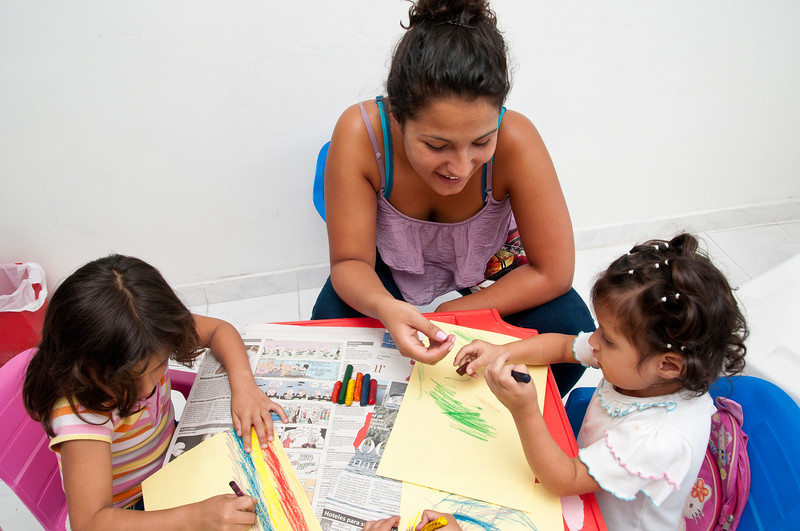 Volunteer helps girls with their drawing.
