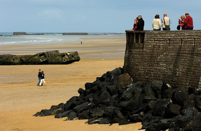 People standing at a stone outcropping overlooking Omaha Beach in France.