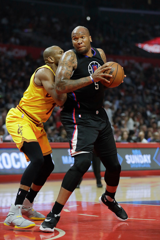 . Los Angeles Clippers\' Marreese Speights, right, is defended by Cleveland Cavaliers\' James Jones during the first half of an NBA basketball game Saturday, March 18, 2017, in Los Angeles. (AP Photo/Jae C. Hong)