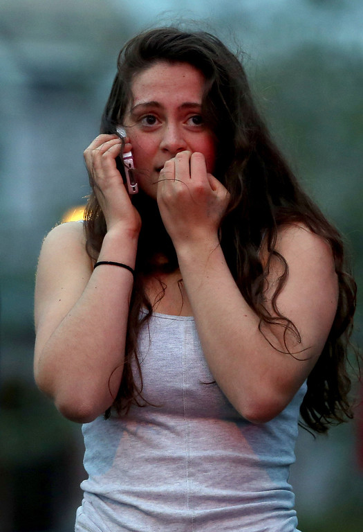 . WATERTOWN, MA - APRIL 19: Resident Rosie Meyer, who said she heard gunshots, reacts while watching police respond on April 19, 2013 in Watertown, Massachusetts. After a car chase and shoot out with police, one suspect in the Boston Marathon bombing, Tamerlan Tsarnaev, 26, was shot and killed by police early morning April 19, and a manhunt is underway for his brother and second suspect, 19-year-old suspect Dzhokhar A. Tsarnaev. The two men, reportedly Chechen of origin, are suspects in the bombings at the Boston Marathon on April 15, that killed three people and wounded at least 170.  (Photo by Mario Tama/Getty Images)