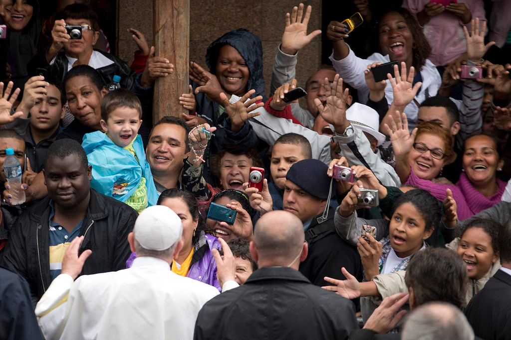 . People greet and take pictures of Pope Francis as he visits the Varginha slum in Rio de Janeiro, Brazil, Thursday, July 25, 2013. Francis on Thursday visited one of Rio de Janeiro\'s shantytowns, or favelas, a place that saw such rough violence in the past that it\'s known by locals as the Gaza Strip. (AP Photo/Victor R. Caivano)
