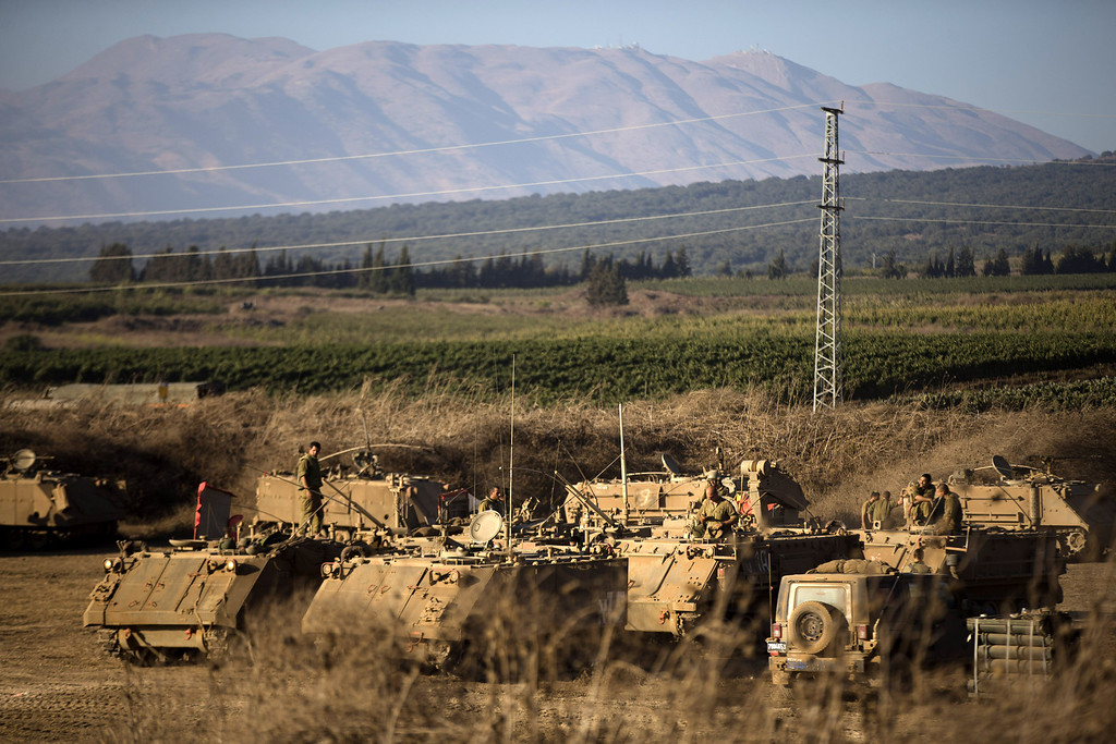 . Israeli soldiers sit on top of their APC\'s at a deployment area during a military exercise on August 28, 2013 near the border with Syria, in the Israeli-annexed Golan Heights. Tension is rising in Israel amid talks of an international military intervention In Syria following reported chemical weapons attacks. (Photo by Uriel Sinai/Getty Images)