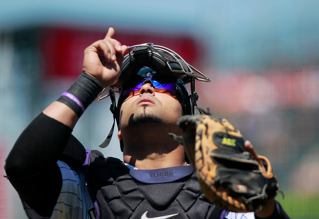 . Colorado Rockies catcher Yorvit Torrealba points upward before the Rockies played the San Diego Padres in a baseball game Wednesday, Aug. 14, 2013, in Denver. (AP Photo/Barry Gutierrez)