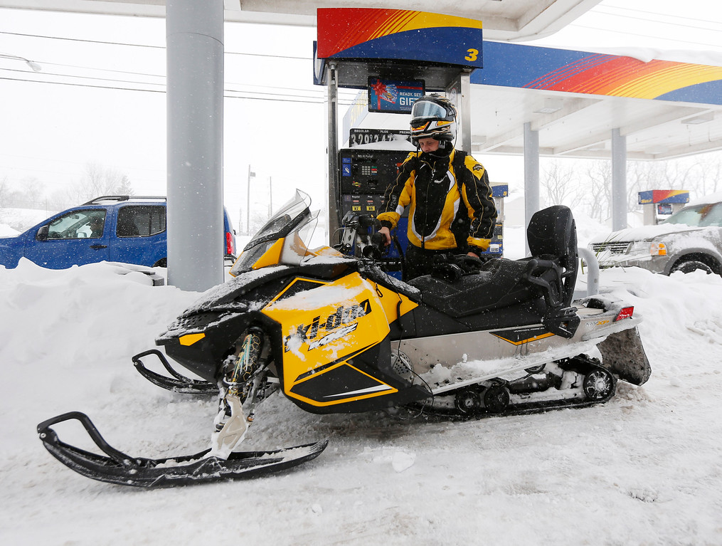 . Jason Burris fuels his snowmobile, Thursday, Nov. 20, 2014, in West Seneca, N.Y.  A new blast of lake-effect snow pounded Buffalo for a third day piling more misery on a city already buried by an epic, deadly snowfall that could leave some areas with nearly 8 feet of snow on the ground when it\'s all done. (AP Photo/Mike Groll)