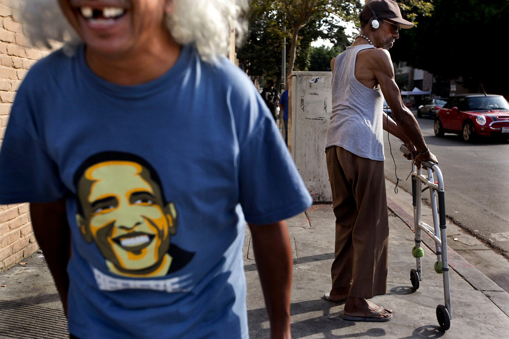 . Cesar Solozano, 60, left, a former homeless man and a recovering drug and alcohol addict, laughs while waiting to cross the street in the Skid Row area of Los Angeles, Wednesday, July 3, 2013. (AP Photo/Jae C. Hong)