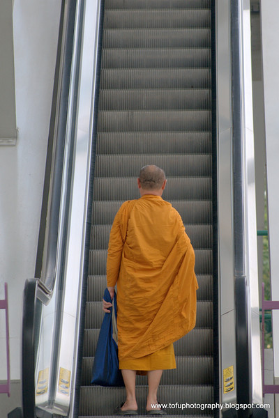 Monk on an escalator  at Krung Thonburi BTS station  in Bangkok, Thailand in December 2009