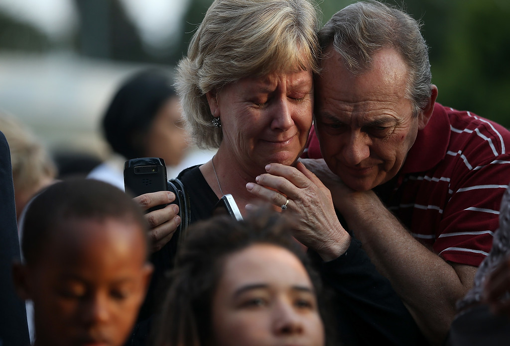 . A couple embraces as they mourn at a shrine of flowers and candles outside the home of Nelson Mandela on December 7, 2013 in Johannesburg, South Africa.  (Photo by Justin Sullivan/Getty Images)