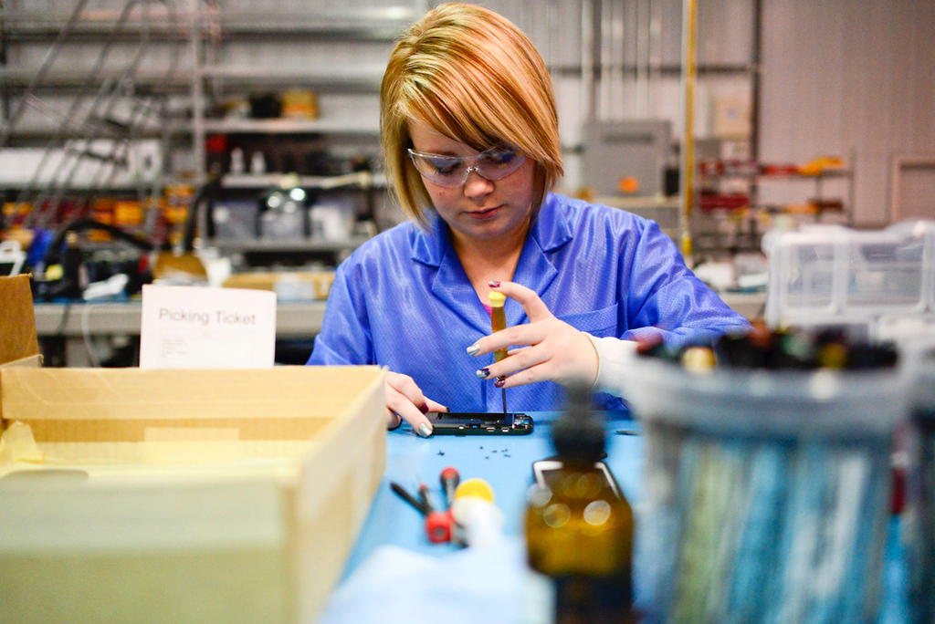 . Jessica Joslyn disassembles a smartphone before it is prepped for painting at the ColorWare facilities in Winona. Joslyn says the most common devices customized are Beat headphones, Macbooks and iPhones. (Pioneer Press: Simon Guerra)