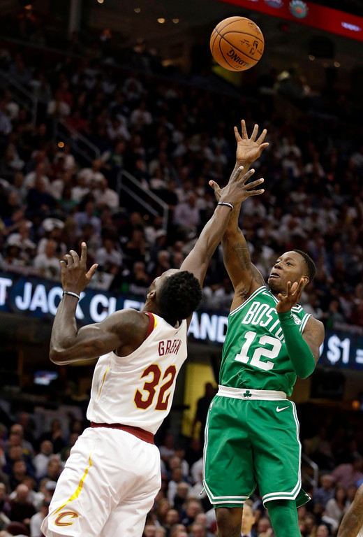 . Boston Celtics\' Terry Rozier (12) shoots over Cleveland Cavaliers\' Jeff Green (32) in the first half of an NBA basketball game, Tuesday, Oct. 17, 2017, in Cleveland. (AP Photo/Tony Dejak)