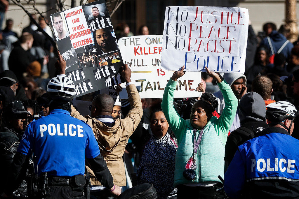 . Protestors gather at a police line outside the Hamilton County Courthouse after a mistrial is declared due to a hung jury in the murder trial against Ray Tensing, Saturday, Nov. 12, 2016, in Cincinnati. Tensing, the former University of Cincinnati police officer, is charged with murdering Sam DuBose while on duty during a routine traffic stop on July 19, 2015. (AP Photo/John Minchillo)