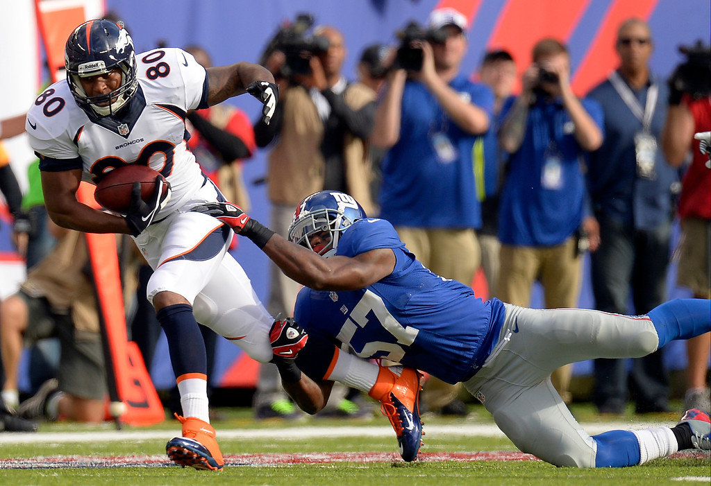 . Tight end Julius Thomas (80) of the Denver Broncos gets caught from behind by outside linebacker Jacquian Williams (57) of the New York Giants after a short gain during the first quarter September 15, 2013 MetLIFE Stadium. (Photo by John Leyba/The Denver Post)