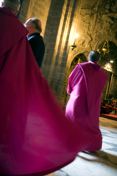Priests with purple robes inside Seville's cathedral during Holy Week, Spain
