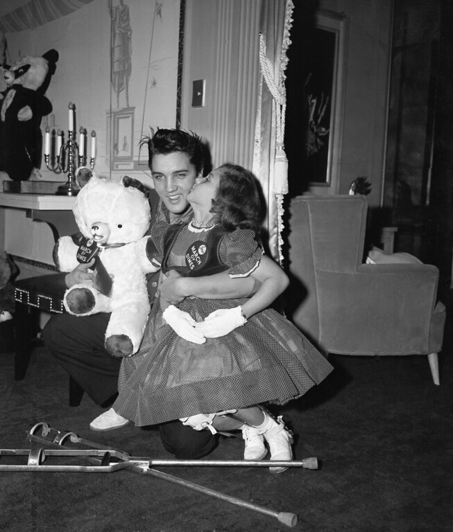. Singer Elvis Presley gets a kiss from eight-year-old Mary Kosloski at his home in Memphis, Tenn., on his 23rd birthday, Jan. 8, 1958.  Kosloski, the 1955 March of Dimes poster child, expresses her appreciation for the toy teddy bears Presley sent to the National Foundation for Infantile Paralysis to be auctioned off to raise money for the March of Dimes.  (AP Photo)