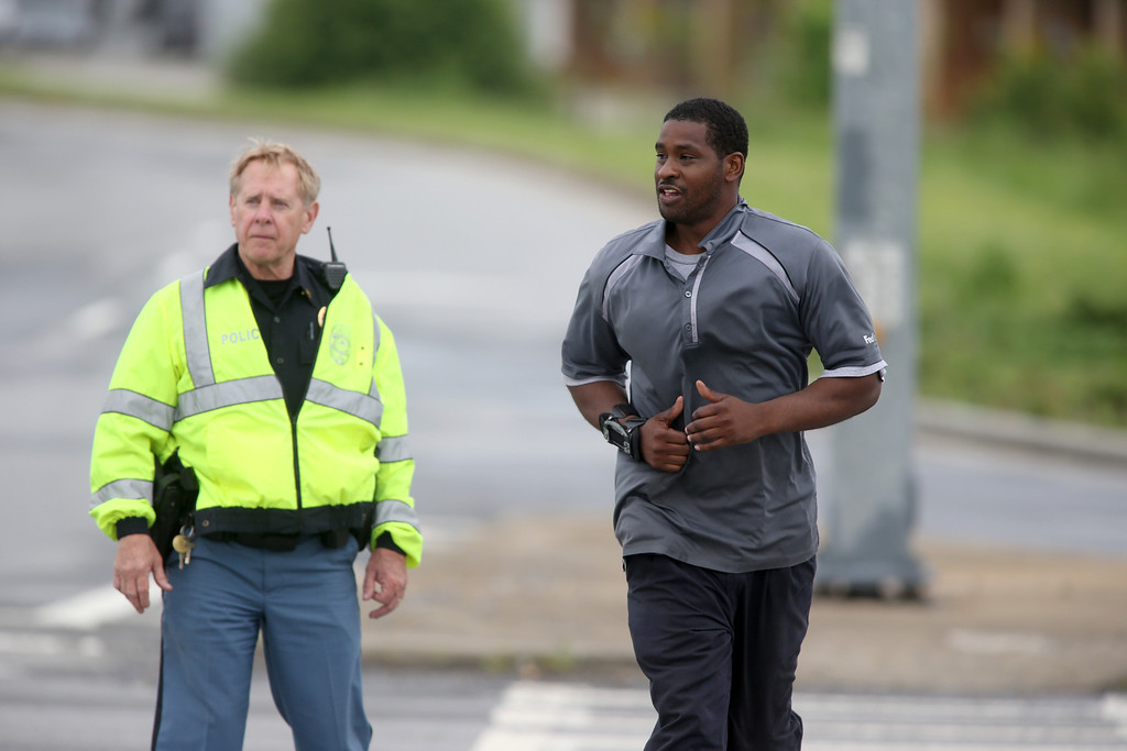 . A Cobb County Police officer, left, escorts a FedEx employee as he crosses McCollum Parkway leaving the blocked off area after an early morning workplace shooting at the Airport Road FedEx facility Tuesday April 29, 2014, in Kennesaw, Ga. A shooter opened fire at a FedEx center wounding at least six people before police swarmed the facility. The shooter was found dead from an apparent self-inflicted gunshot wound. (AP Photo/Jason Getz)
