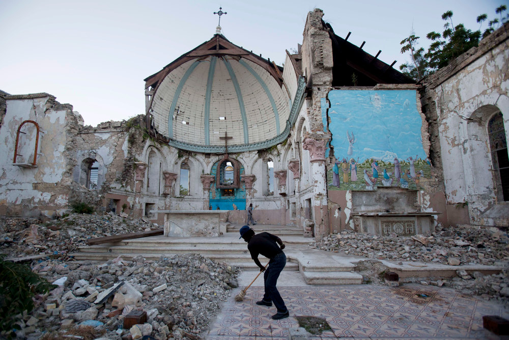 Description of . A man sweeps an exposed tiled area of the earthquake-damaged Santa Ana Catholic church, where he now lives, in Port-au-Prince, Haiti, Saturday, Jan. 12, 2013. Haitians recalled Saturday the tens of thousands of people who lost their lives in a devastating earthquake three years ago, marking the disaster\'s anniversary. Most of the rubble created by the quake has since been carted away but more than 350,000 people still live in displacement camps. (AP Photo/Dieu Nalio Chery)